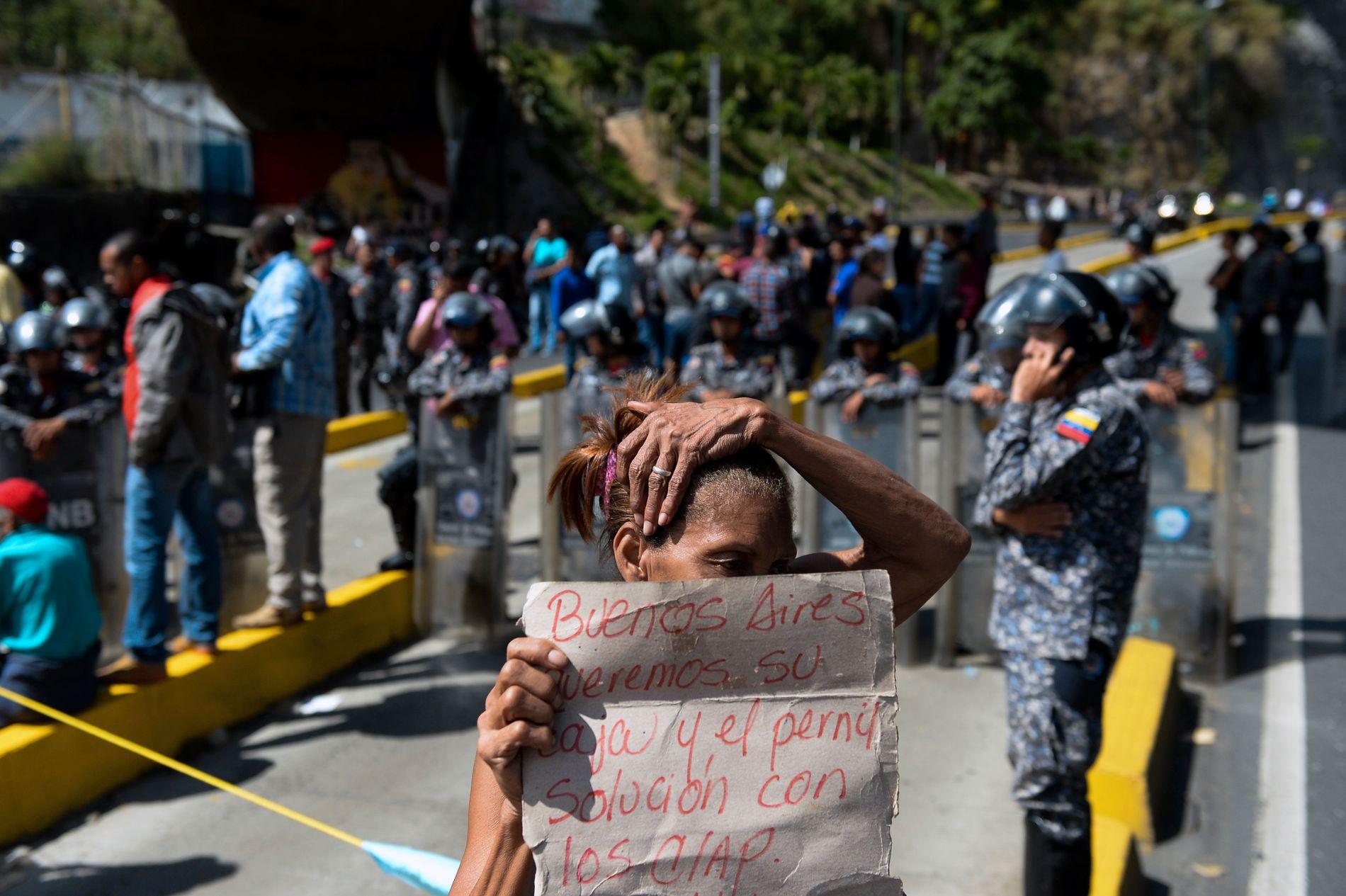 PROTESTER: En kvinne i Caracas holder opp en plakat i protest mot landets president, som brøt løftet om årets juleskinke.