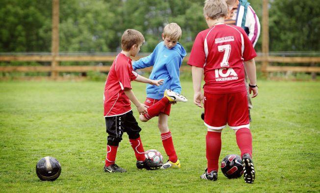 SJEKKER KNOTTER: Erik Mårtensson sjekker om knottene på fotballskoa er fri for jord og gress på treningsfeltet i Vikersund. 14-åringen er den eneste av fire søsken som fortsatt spiller fotball. De andre fortsatte med andre idretter i stedet.