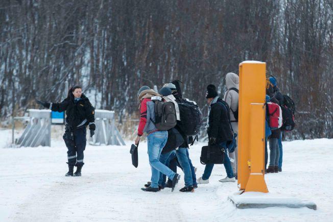 NULL I DESEMBER: En norsk politikvinne avbildet sammen med en gruppe asylsøkerne som ankom grensestasjonen ved Storskog i forrige måned. Siden 30. november har ingen asylsøkere kommet inn i landet fra samme sted.