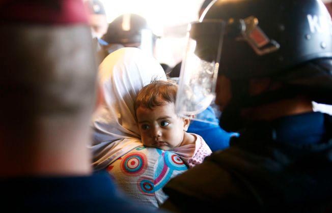 POLITIBESKYTTELSE: En liten jente ser på politimennene som holder vakt ved flyktningene på jernbanestasjonen Bicske i Ungarn.