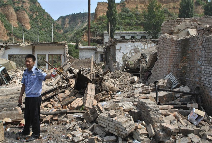 KRAFTIG SMELL: En politibetjent står ved siden av bygningen som eksploderte i Liugou Coal gruvedrift i Linfen i nord-kina. Foto: AP