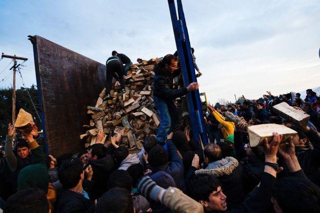 KAOS: Flere hundre mennesker strømmet til da lokale myndigheter delte ut vedkubber til flyktningene på den gresk-makedonske grensen søndag.
