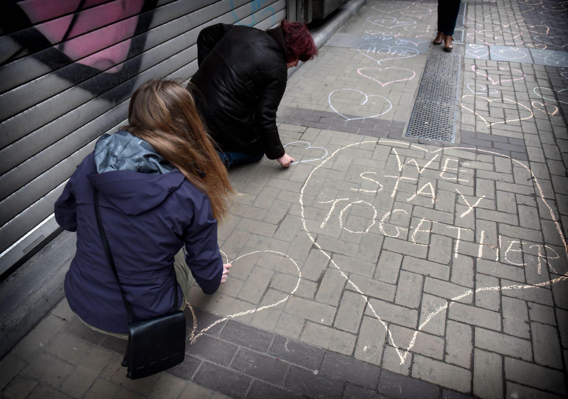 MINNES: Sara Van Den Eynden (grønn kåpe) og hennes kolleger i et firma som holder til rett over T-bane stasjonen Maalbeek som ble rammet av terroren, tegner hjerter flere hundre meter nedover fortauet utenfor bygningen. Stasjonen er fortsatt stengt, men metroen har begynt å kjøre igjen. Vaktholdet er svært strengt, all fotografering er forbudt. Foto: HARALD HENDEN, VG