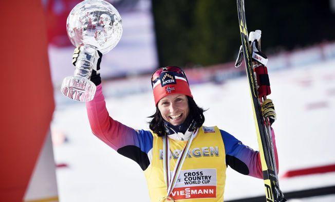 FORTSETTER: Marit Bjørgen løfter her det synlige beviset på sammenlagtseieren i verdenscupen under vinterens renn i Holmenkollen.