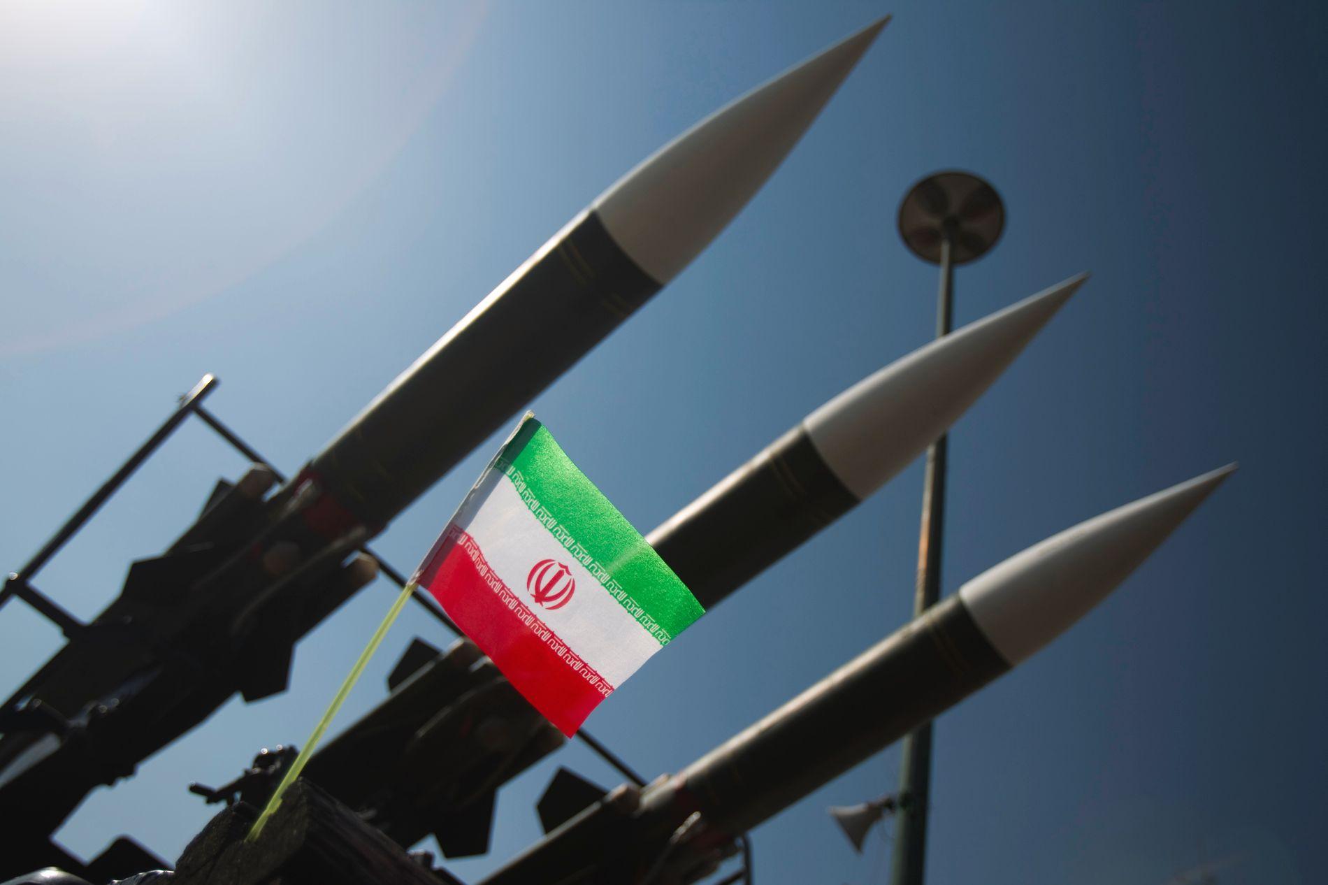 RAKETT-TRØBBEL: Iran mener USAs sanksjoner etter landets rakett-oppskytning bryter atomavtalen. USA frykter romrakett-programmet kan være et skalkeskjul for våpenutvikling. Bildet viser russiske missiler ved siden av et iransk flagg under en tidligere krigs-utstilling