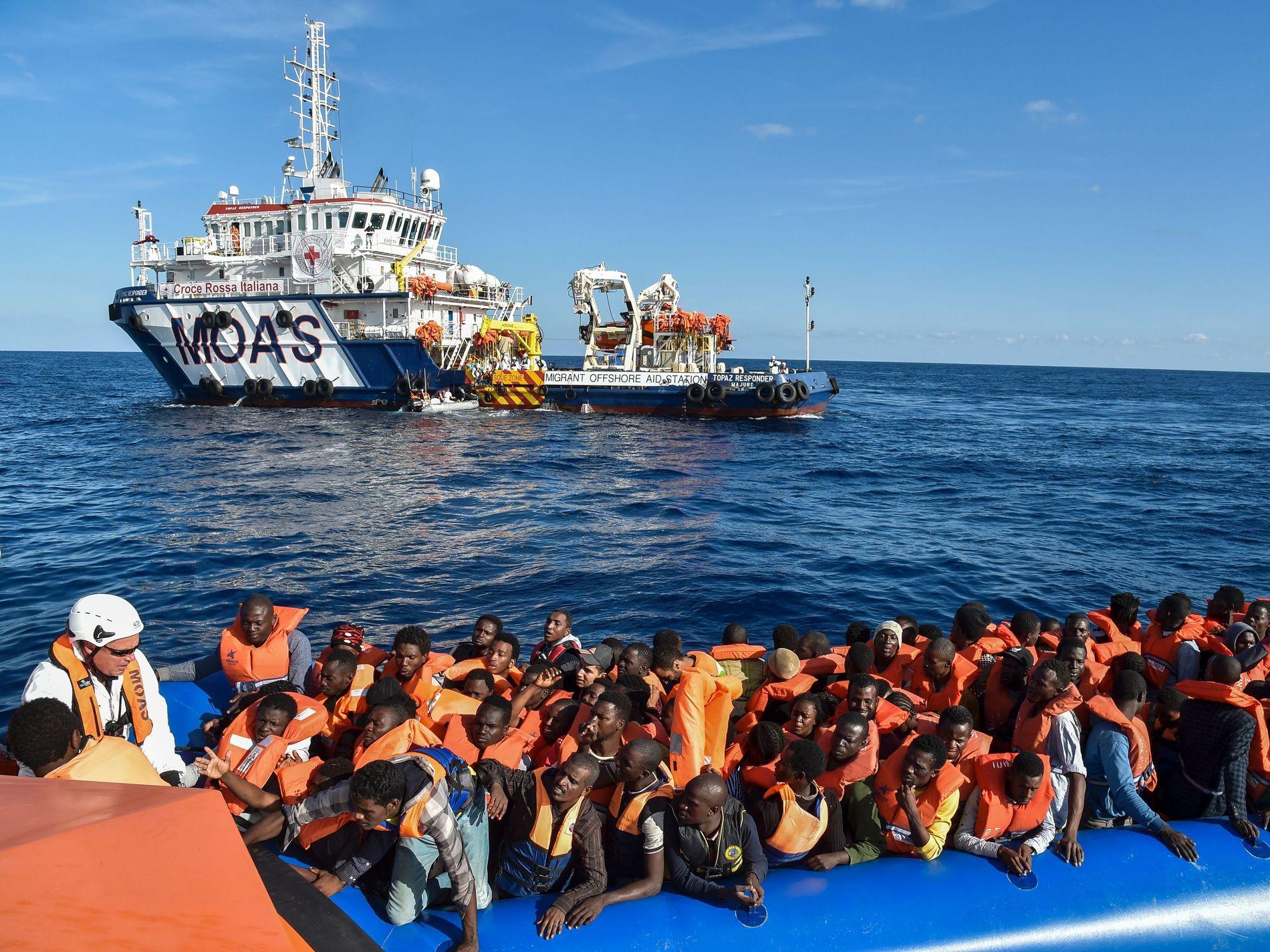 I SISTE ØYEBLIKK: Kystvakten til Libya avventer situasjonen mens flyktninger i en overfylt gummibåt venter på å bli reddet av et skip fra italienske Røde Kors. Foto: AFP