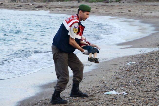 OVER MIDDELHAVET: Her bærer en mann fra militærpolitiet i Tyrkia bort Alan Kurdi, som ble funnet død med to andre på stranden i Bodrum. Båten han og familien satt i skulle til Kos, men kantret i Middelhavet. Moren Rehan og broren Galib ble senere funnet døde. Faren Abdullah overlevde forliset.