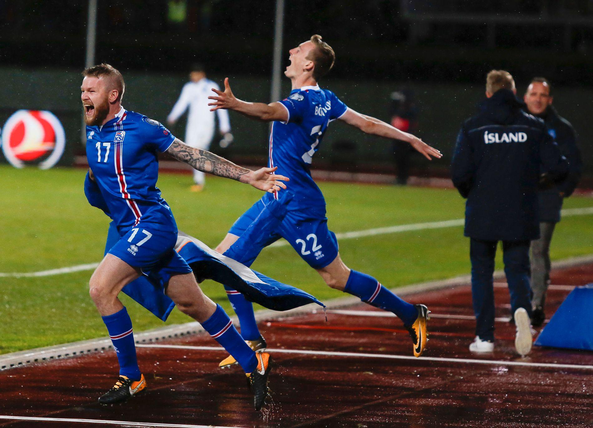 ELLEVILLE SCENER: Aron Gunnarsson (til venstre) og Jon Dadi Bödvarsson jubler når kampen er over. I bakgrunnen takker landslagssjef Heimir Hallgrimsson sin avtroppende Kosovo-kollega Albert Bunjaki for kampen. Foto: AP