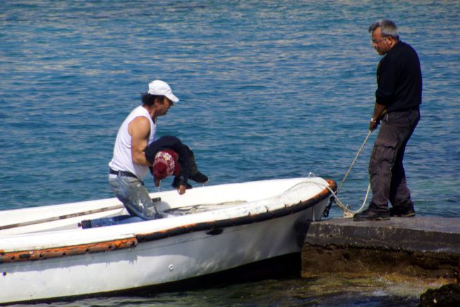 DRUKNET I MIDDELHAVET: Et barn som druknet i et av mandages båtforlis blir båret i land på øya Aegean på Rhodos, Hellas. Barnet var en av minst tre mennesker som omkom da en trebåt med flyktninger gikk på grunn mandag.