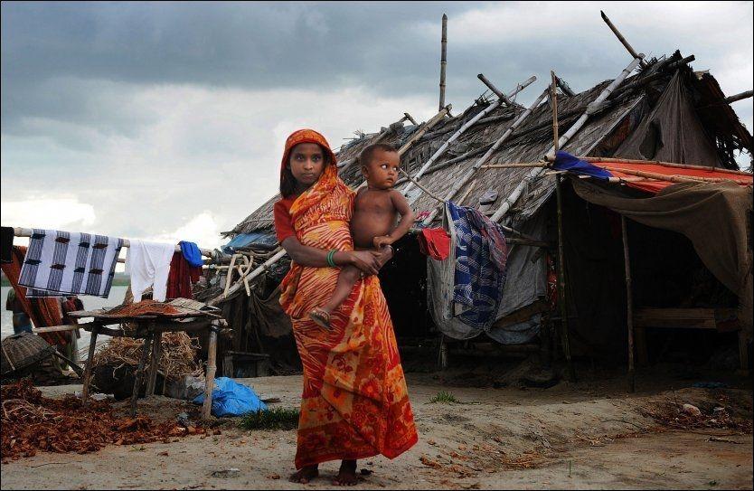 I SLUMMEN: Den unge kvinnen Nargis holder et barn i Dhaka-slummen i Bangladesh. Engelske forskere tror landet vil kunne avskaffe ekstrem fattigdom i løpet av hennes levetid. Foto: MUNIR UZ ZAMAN / AFP / NTB SCANPIX