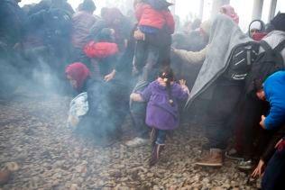 FLYKTER: Mennesker flykter etter at makedonsk politi avfyrer tåregass mot flyktningene som forsøker å ta seg over til andre siden av grensen