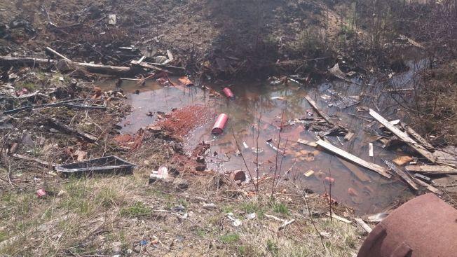 I VANNET: Fylkesmannen frykter at giftstoffer fra avfallet har eller vil spre seg til grunnvannet. Grunneier og de som står bak virksomheten er nå politianmeldt for brudd på forurensingsloven.