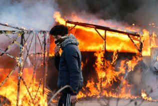 En ung flyktning avbildet foran flammer i «Jungelen» i Calais, mandag.