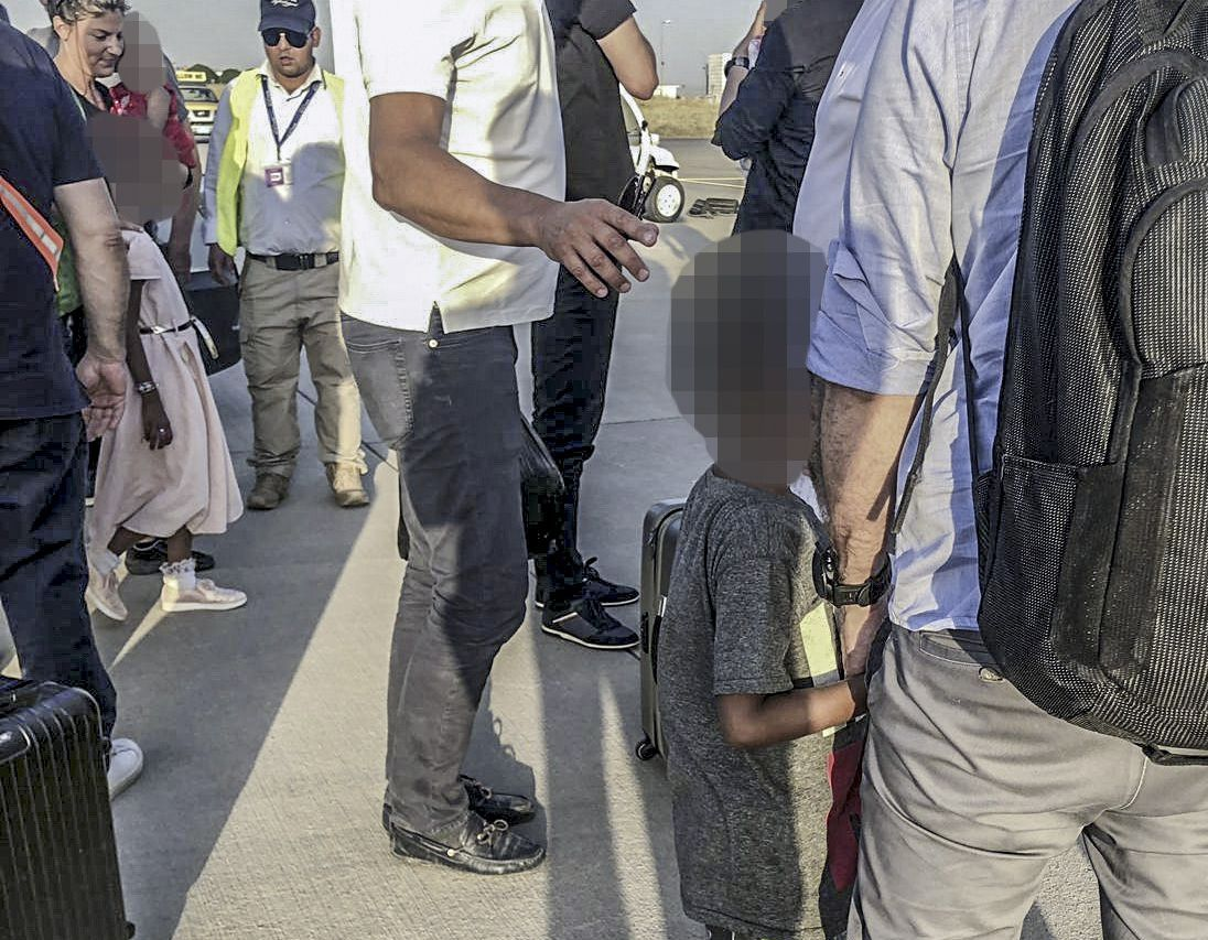 EN HÅND Å HOLDE I: Ett av de norske barna på flyplassen i Erbil før hjemtransport til Norge.