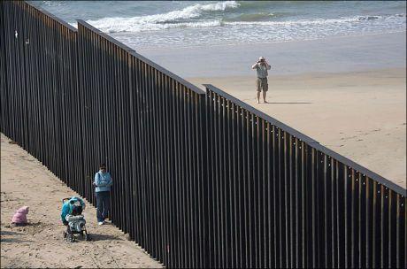 STENGT: Lizeth Romero (24) står inntil grensegjerde mens hun venter på sin kjæreste. På amerikansk side står en mann og tar bilde av grensegjerdet mellom Mexico og USA. Både Obama og McCain ønsker strengere grensekontroll. Foto: AP