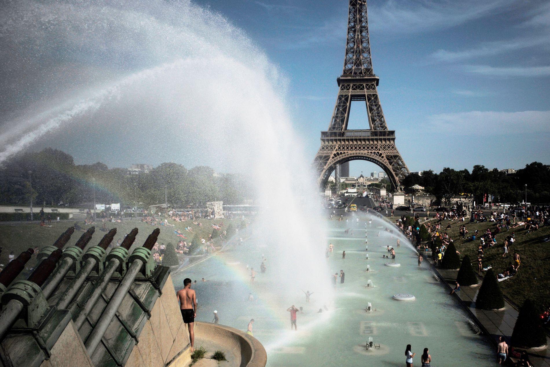 Mennesker kjøler seg ned i Trocadero-fontenen foran Eiffeltårnet i Paris, under den første hetebølgen i slutten av juni. Nå kommer ekstremvarmen tilbake til den franske hovedstaden.