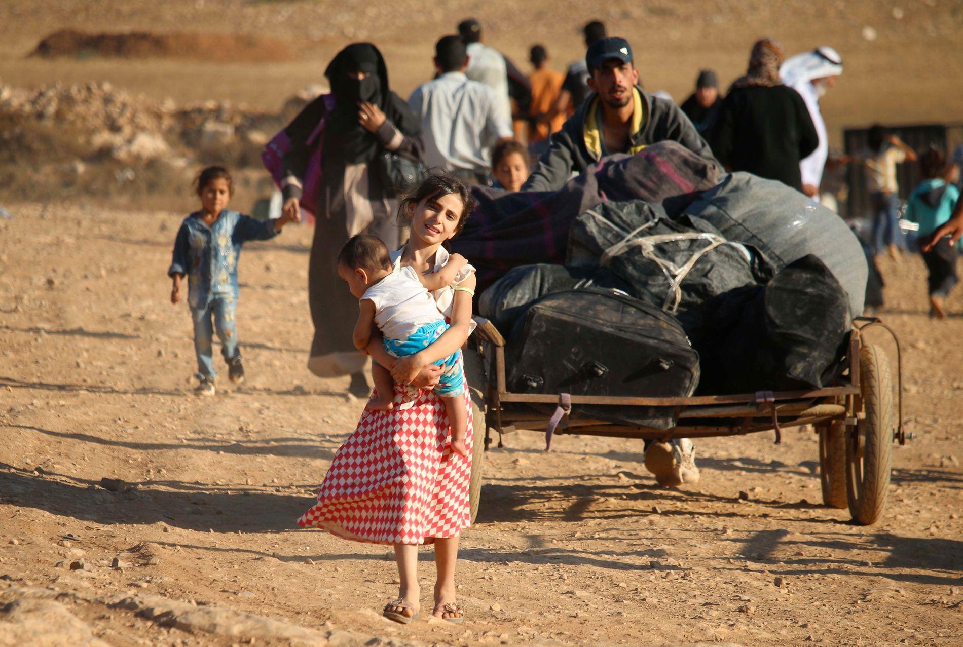 PÅ FLUKT: En syrisk flyktningfamilie i ferd med å krysse grensen mellom Jordan og Syria i august i fjor. Familien er blant de 66.000 syriske flyktningene som returnerte til hjemlandet i fjor.