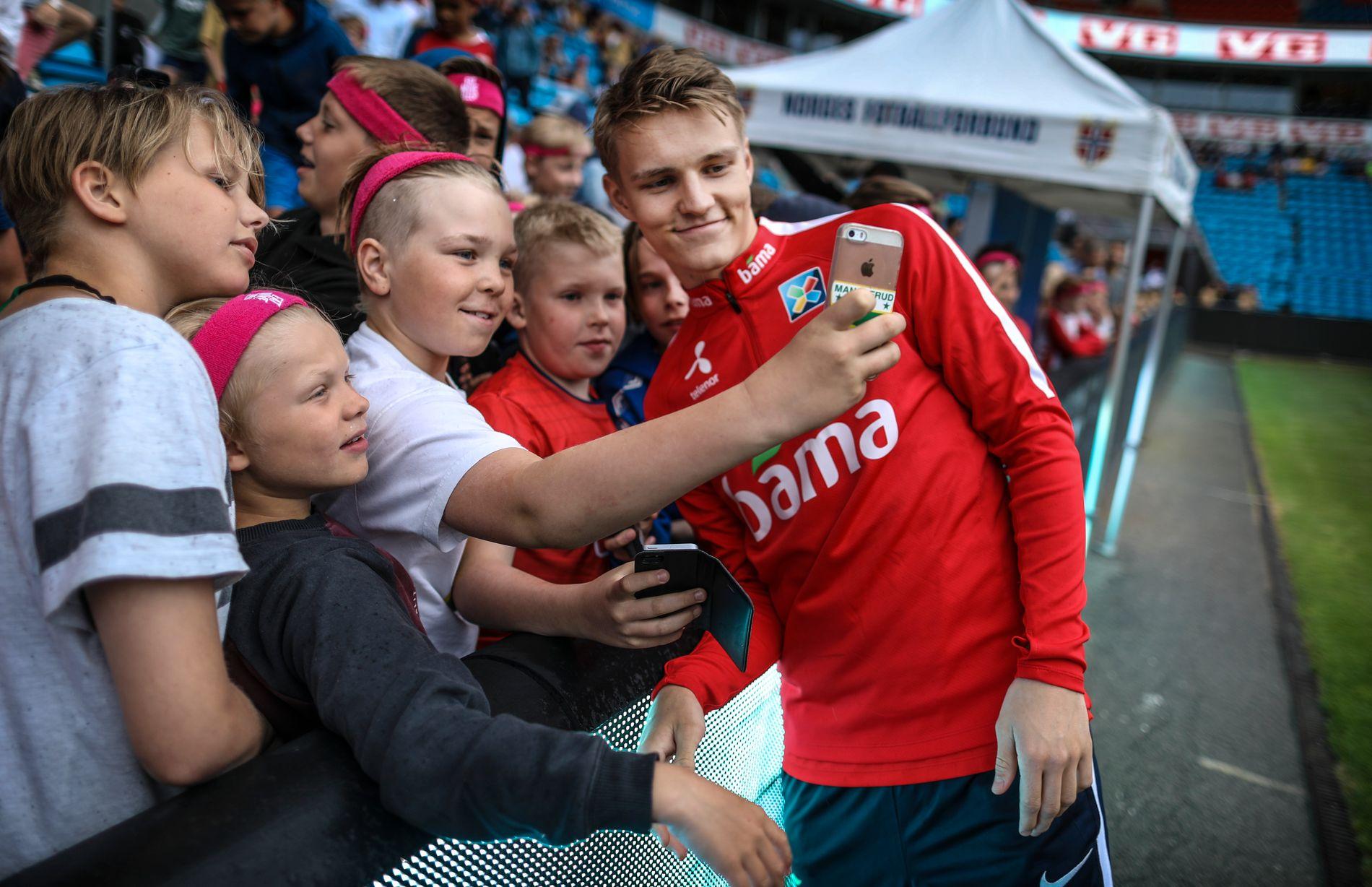 FANSENS FAVORITT: Norges Fotballforbund hadde besøk av en rekke klubber på «Åpen dag» under A-landslagets trening mandag ettermiddag. Her blir det sikret en selfie med Martin Ødegaard.