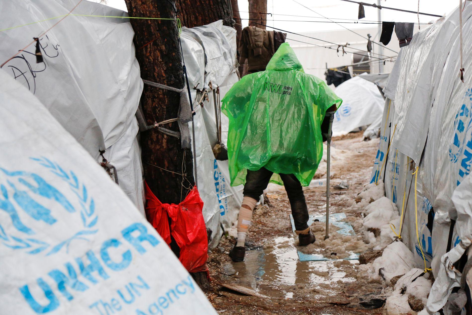NORSK REGNDRAKT: Snø og regn har skapt store vanndammer inne i Moria. Her hopper en flyktning over en sølepytt ikledd regnponcho fra den norske dagligvarekjeden Kiwi.