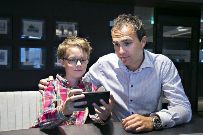 MOBILGLAD: Victor viser pappa hvordan han har handlet blant annet virtuelle kister i spill på mobiltelefonen.