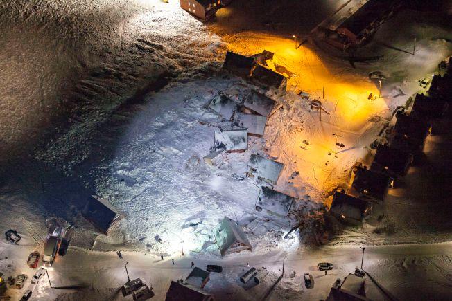 FLYTTET ET BOLIGFELT: Husene ligger hulter til bulter og delvis nedgravd i snø etter lørdagens skred fra fjellet Sukkertoppen og ned mot spisshusene i Longyearbyen på Svalbard. Ett av husene var allerede revet da bildet ble tatt, for å sikre atkomst til veien som går gjennom boligfeltet.