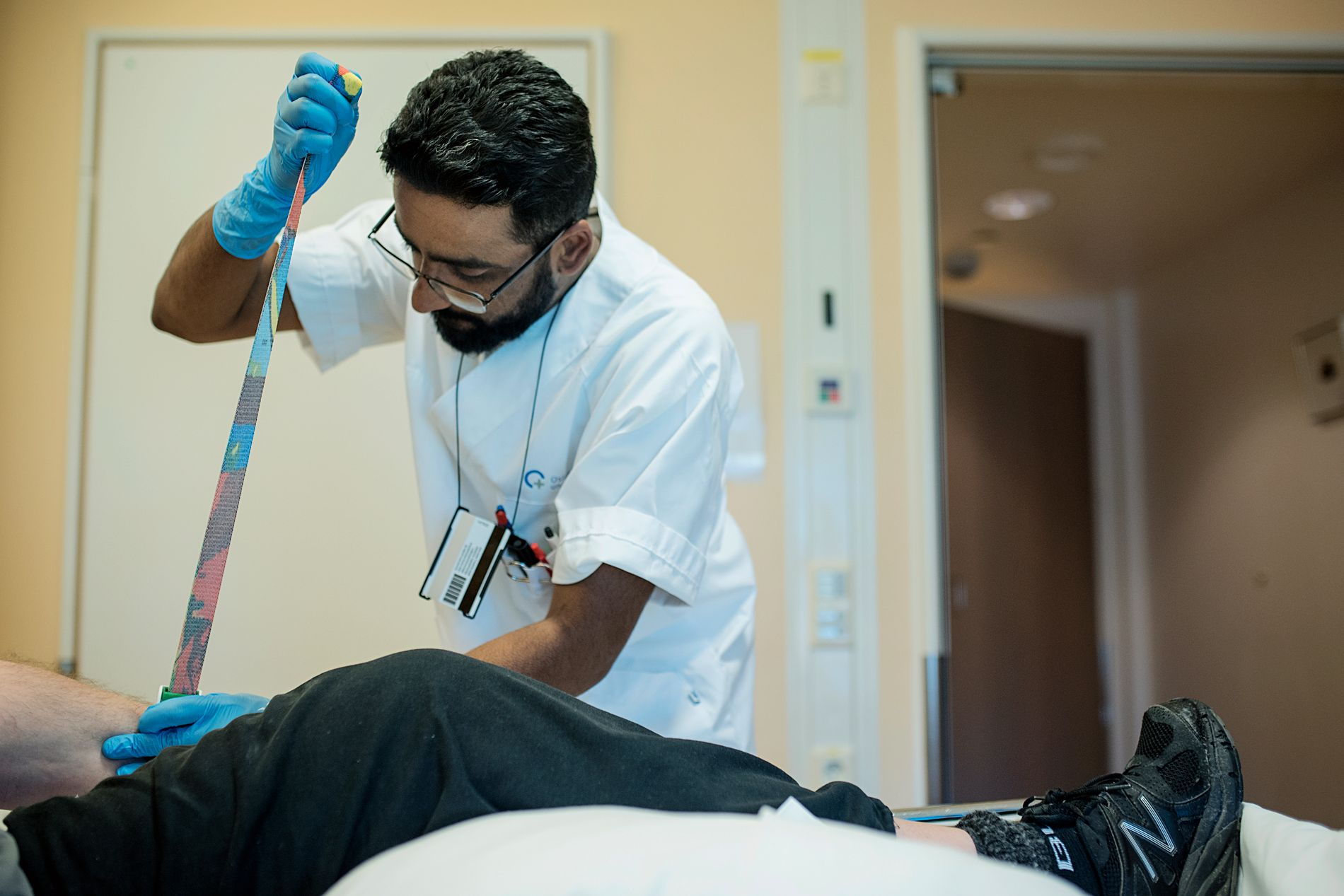 TUNGT ARBEID: Sykepleier Ansar Qadeer (30) tar blodprøver på en av sine pasienter på Nevrologisk avdeling på Rikshospitalet. – Yrket passer godt for menn, fordi det er fysisk krevende, sier han.