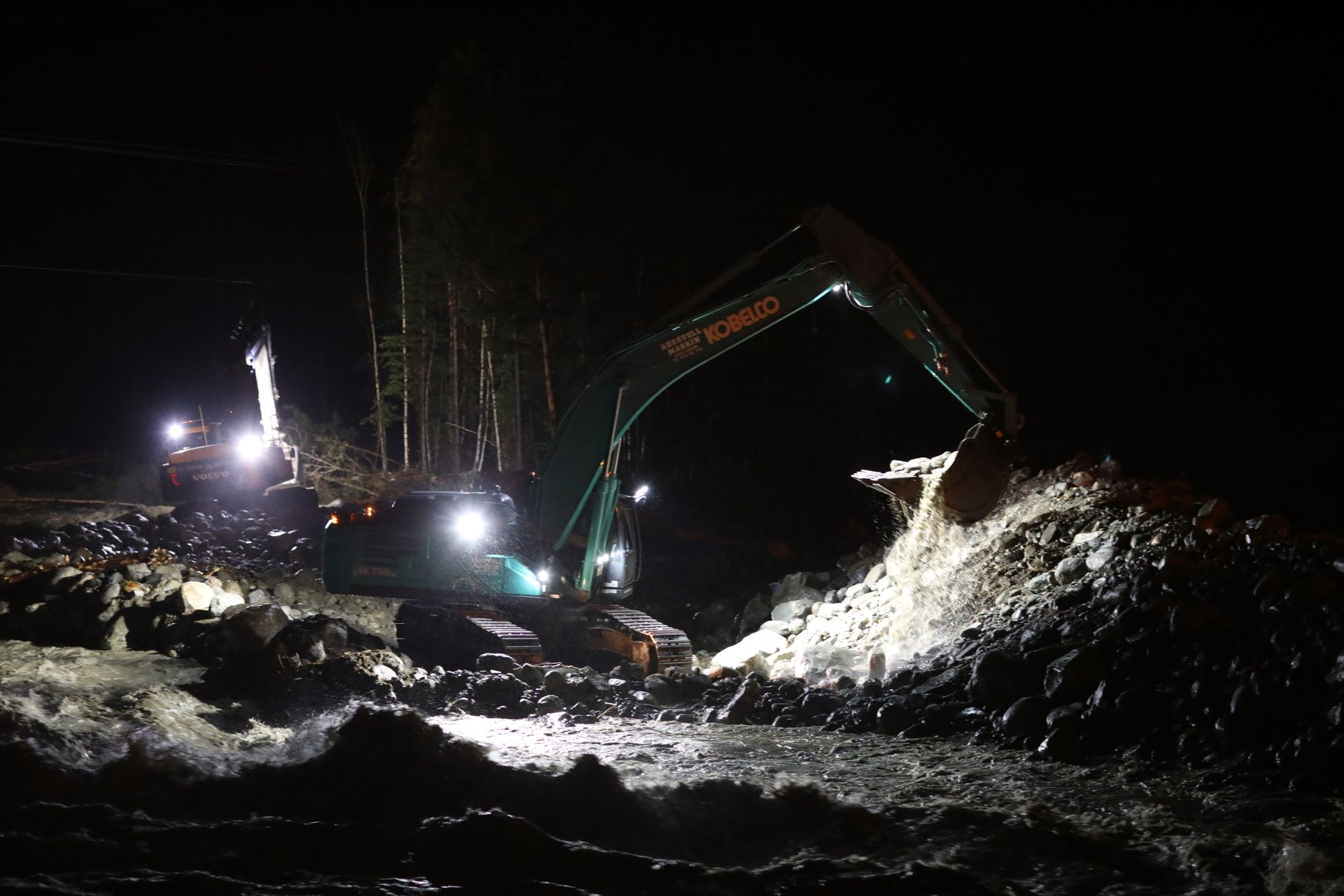 KRISETILTAK:  Krisetiltakene fortsetter langs veien mot Skjåk utover natten. Store gravemaskiner rydder i eleven for bedre vannføringen.
