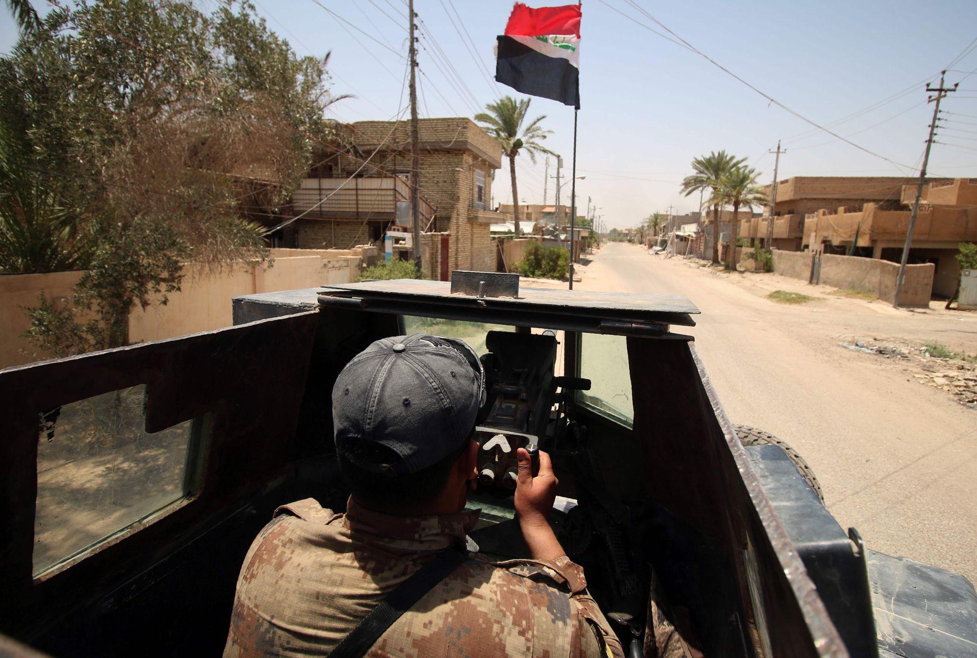 OVER: Den månedslange offensiven mot IS i Fallujah er nå avsluttet, ifølge AP. Her kjører et medlem av antiterror-styrkene i byen 23. juni.