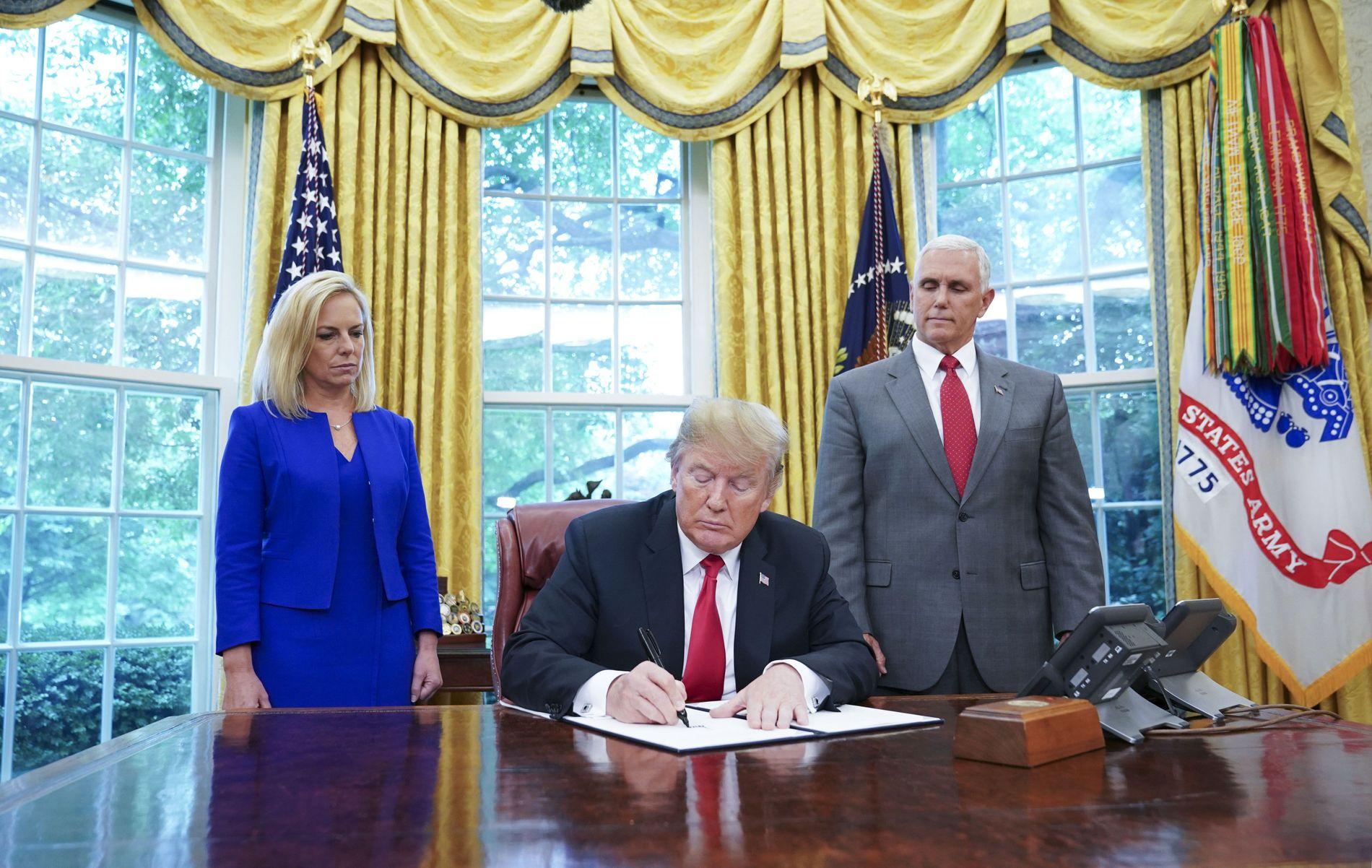 UNDERTEGNER: USAs president Donald Trump signerer et direktiv som stanser oppsplittingen av familier som har krysset grensen ulovlig. Til hans venstre står Kirstjen Nielsen, sjef for innenlands sikkerhet, til hans høyre står visepresident Mike Pence.