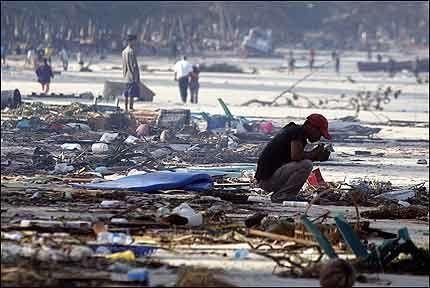 SORG: En ung mann sitter i stille ettertenksomhet på stranden i Patong på Phuket mandag morgen. Foto: REUTERS