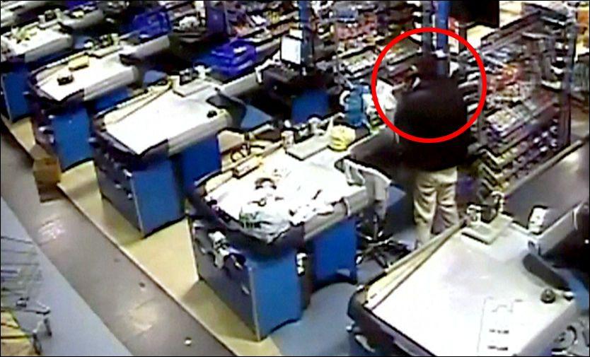 I TELEFONEN: Dette stillbilde fra overvåkningsvideoen viser at en mann går mellom kassaapparatene på kjøpesenteret mens han snakker i telefonen. Mannen er den samme politiet tror er den norsk-somaliske 23-åringen. Foto: OVERVÅKNINGSKAMERA