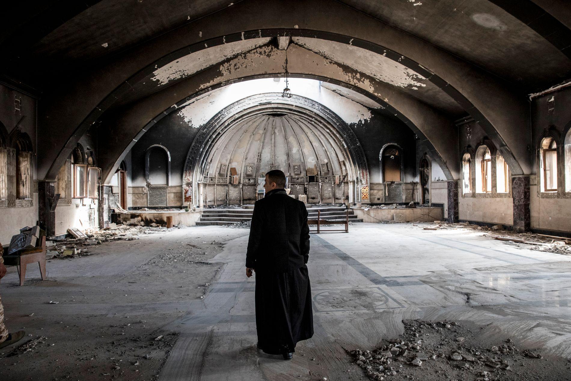 RESTENE ETTER IS: Presten Danyal vandrer gjennom en nedbrent og vandalisert kirke i Qaraqosh i Mosul i mars i år.