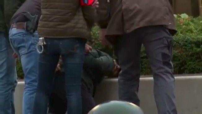 POLITIAKSJON: Her pågriper belgisk politi en person i bydelen Molenbeek i Brussel søndag formiddag. Totalt er minst åtte personer tatt i Belgia i forbindelse med terrorangrepet.