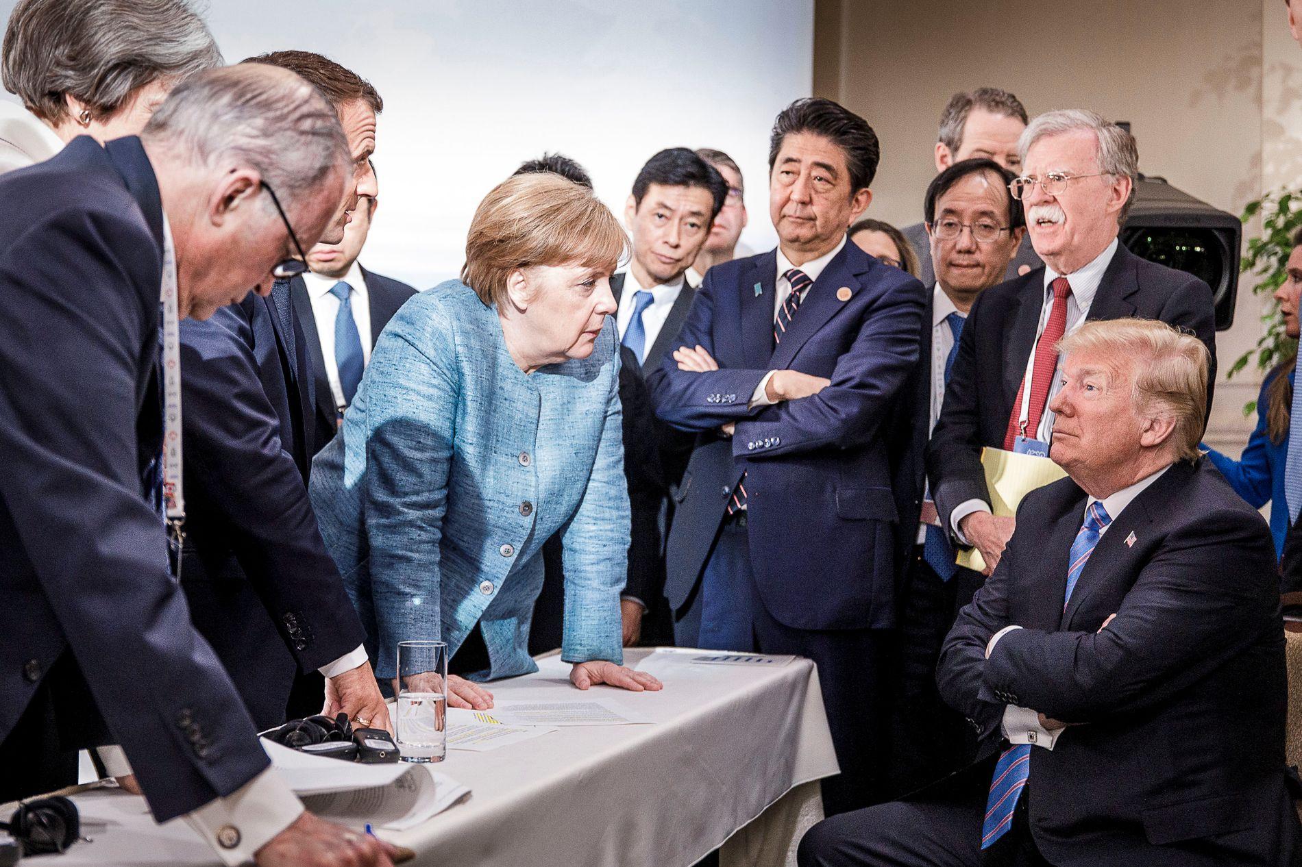 VERDEN MOT TRUMP: Tysklands forbundskansler Angela Merkel ser ut til å ha noe hun vil si til USAs president Donald Trump. Japans statsminister Shinzo Abe står med armene i kors, mens man også kan skimte Frankrikes Emmanuel Macron og Storbritannias Theresa May til venstre for Merkel.