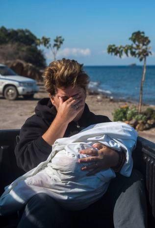 PREGET: En av innbyggerne tar til tårene med den døde kroppen til et barn som druknet utenfor strendene nord på Lesbos i armene.