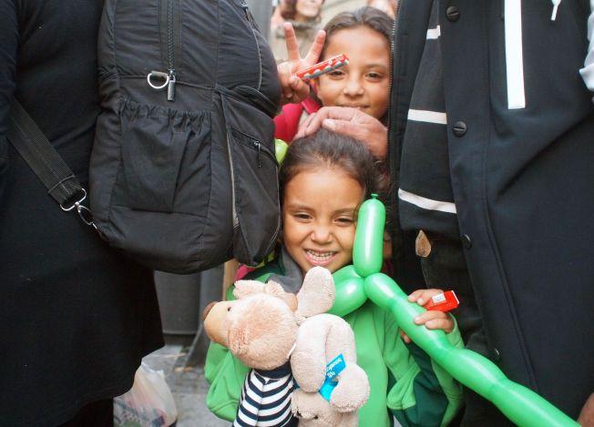 FIKK GAVER: Disse to syriske jentene fikk ballonger og bamser av ukjente mennesker som hadde møtt opp på jernbanestasjonen i München for å ønske flyktningene velkommen.