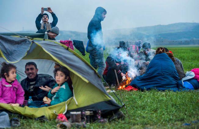HIT, MEN IKKE LENGER: Familien fra Irak prøver å holde varmen rundt et bål i Idomeni-leiren nord i Hellas. Etter at Makedonia stengte grensen for noen dager siden, er det her flyktningene og migrantene hoper seg opp.