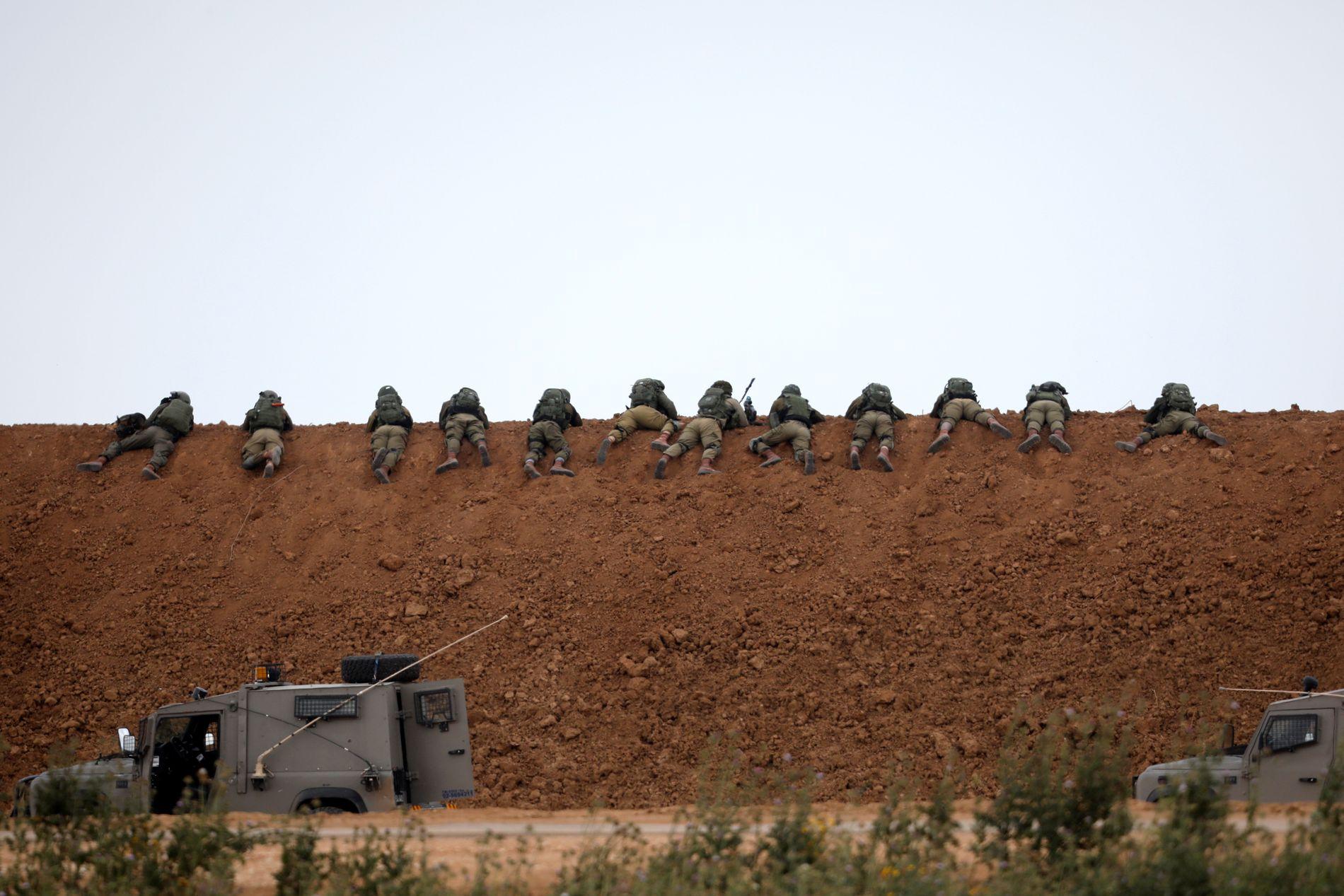 SKJØT HERFRA: Israelske soldater fotografert bak en jordvold, på den andre siden av grensegjerdet mot Gaza, under demonstrasjonene på fredag.