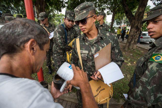 AKSJON: VG fulgte med da 40 soldater og 24 kommunalt ansatte oppsøkte over tusen husstander i slumområdene i Recife, Brasil søndag morgen. Her får hæren utlevert insektgift.