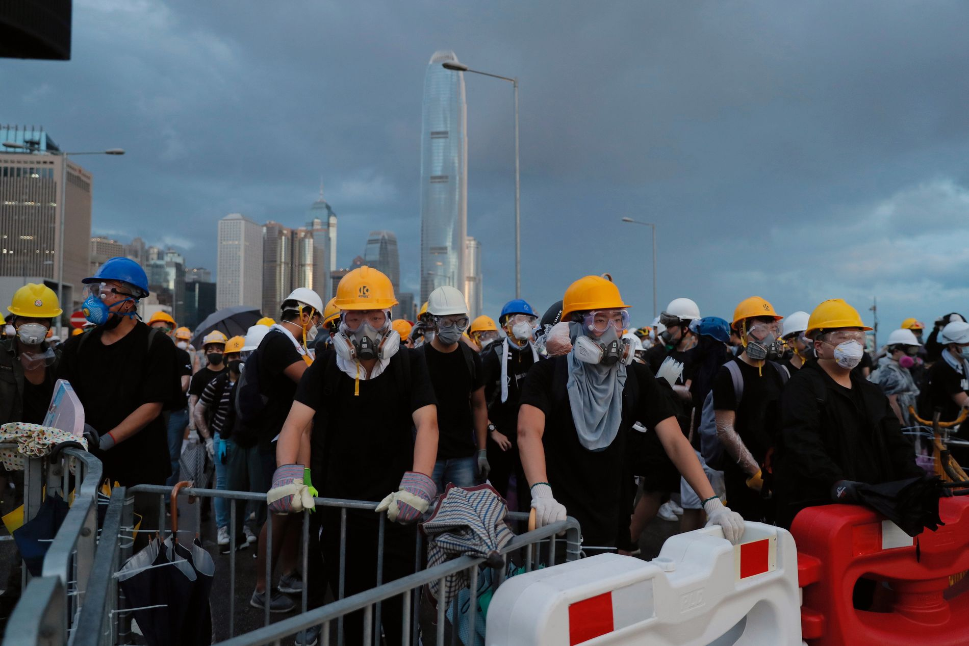 SPERRER VEIER: Demonstranter med hjelmer og gassmasker forsøker å sperre en vei som leder inn til området der det markeres at det er 22 år siden Hongkong ble overført til Kina.