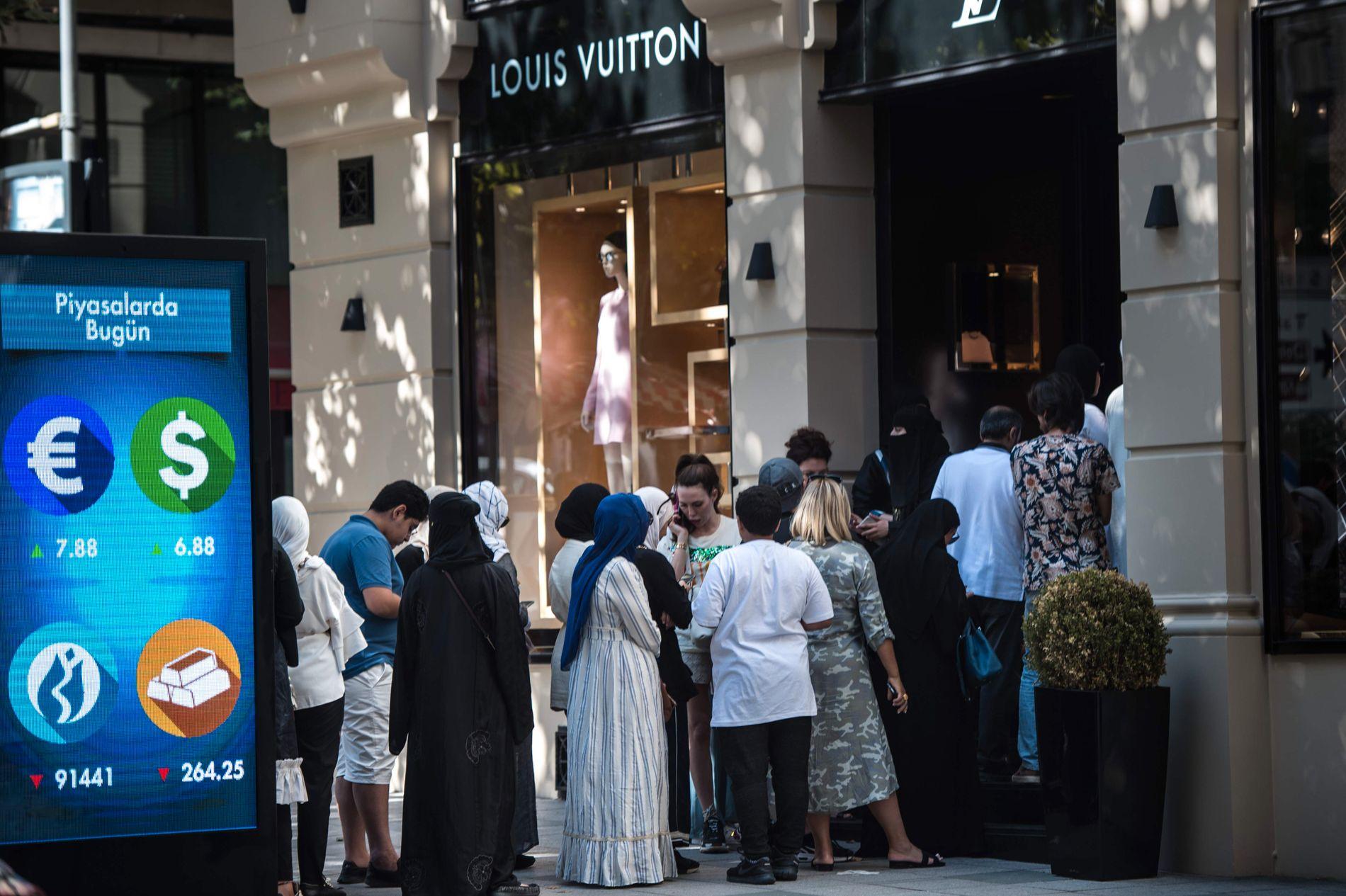 BILLIGERE LUKSUS: Turistene sto mandag i kø utenfor Louis Vuitton-butikken i Istanbul. Luksusvarene er blitt billigere på grunn av det kraftige valutafallet, demonstrert ved plakaten til venstre.
