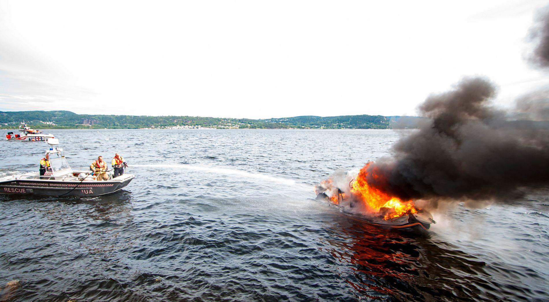 FULL FYR: Brannmannskaper forsøker å slukke brannen på båten til Caroline Graham Hansen og familien i Drammensfjorden torsdag.
