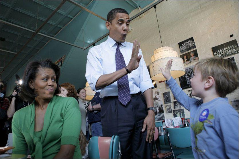 HIGH FIVE: Lille Owen Raup (3) hilser på presidentkandidaten Barack Obama, som har tatt med kona på en restaurant for å hilse på restaurantgjestene og for å sanke stemmer. Foto: AP