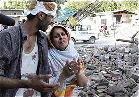 FORTVILET: Denne moren mistet datteren sin da skolen i Muzaffarabad kollapset. Mannen forsøker å trøste til ingen nytte. Foto: EPA