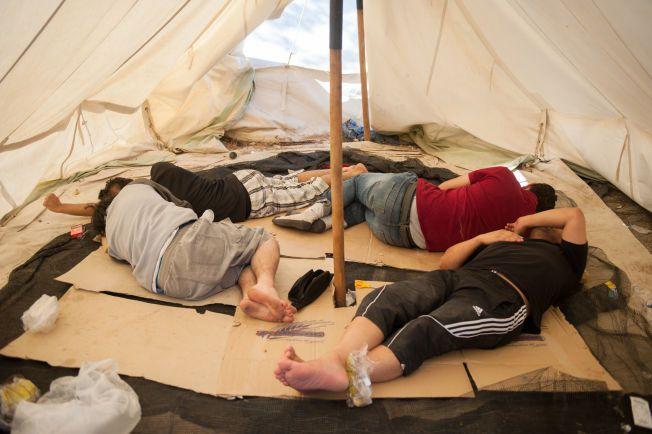 IKKE SENGER: I mangel på tepper og madrasser sover flyktningene på pappesker i telt ved Moria-campen.