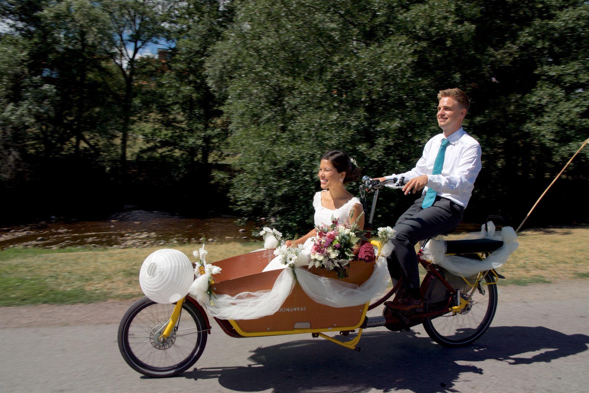 BRUDE-SYKKEL: Brudgom Eivind Trædal (32) med grønt slips og bruden i hvit, ermeløs brudekjole med langt slep, Lan Marie Nguyen Berg (31, kjører transportsykkel i full fart nedover Markveien ved Akerselva på vei til sitt eget bryllup lørdag.