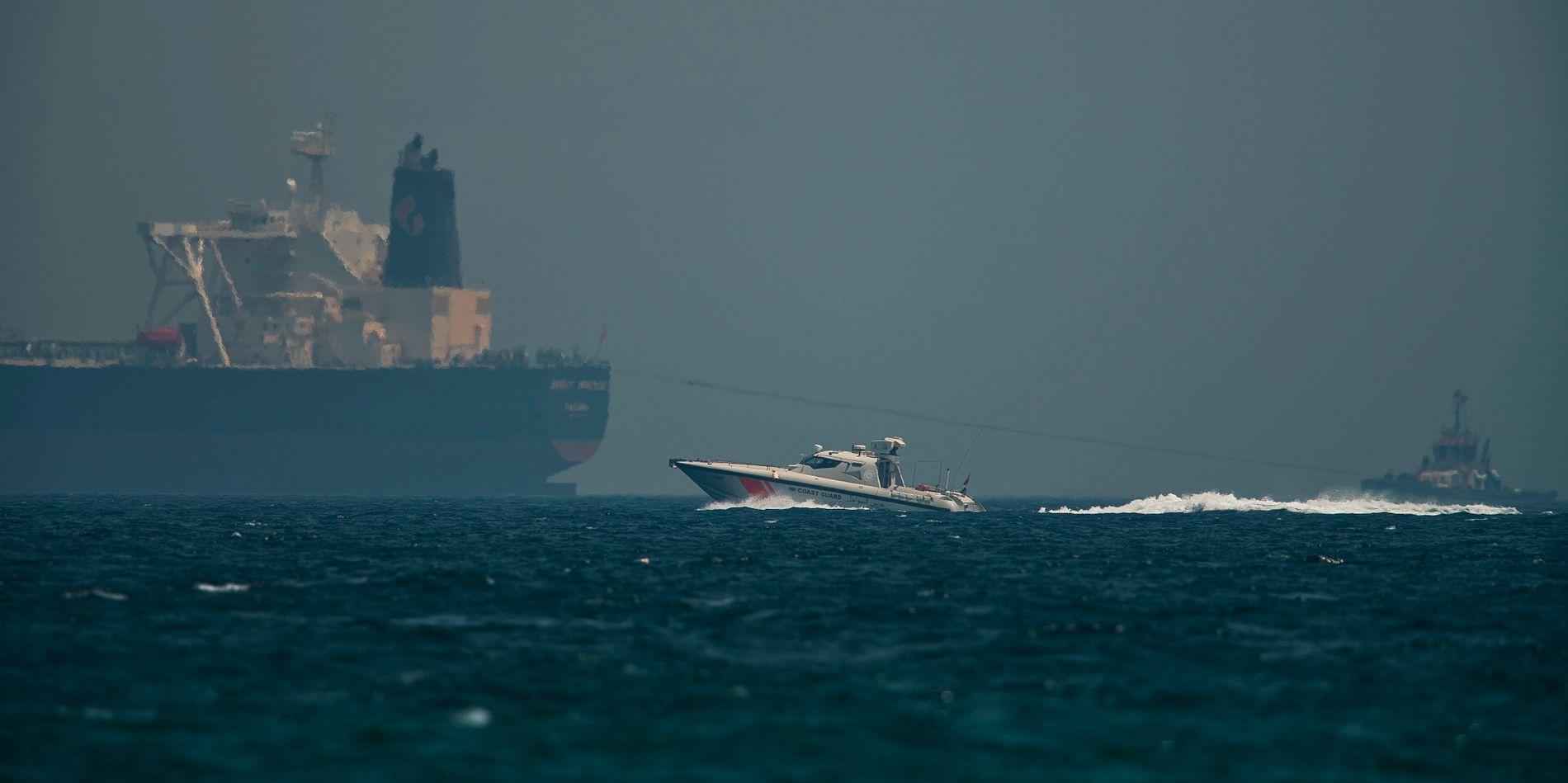 PATRULJERER: Et hurtiggående kystvaktskip fra Emiratene passerer en oljetanker utenfor kysten av havnebyen Fujairah ved Omanbukta 13. mai i  år.