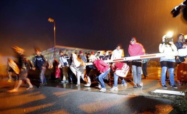 VELKOMMEN TIL ØSTERRIKE: Her passerer flyktningene grensestasjonen Hegyeshalom på sin vei inn i Østerrike og videre til Tyskland tidlig lørdag morgen.