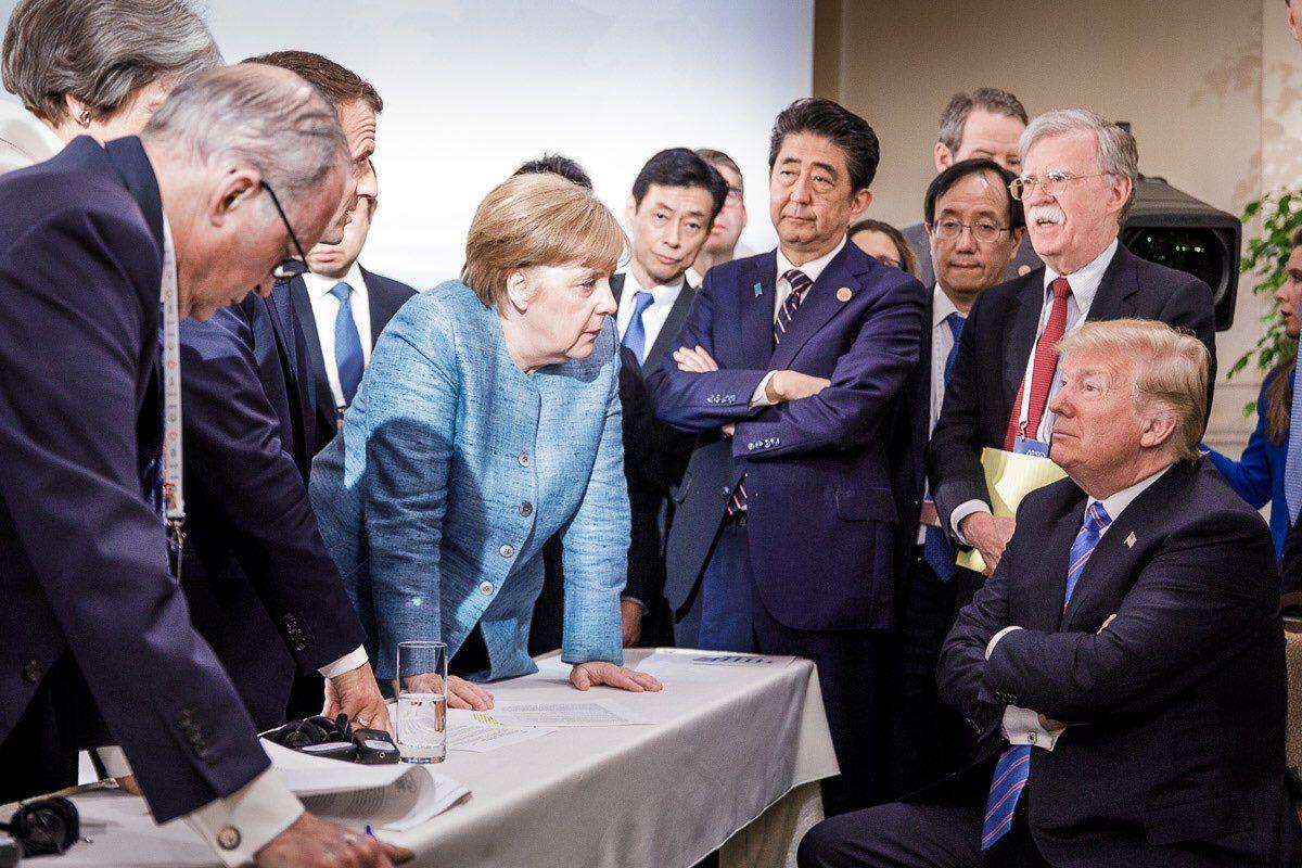 SNUDDE: Tysklands forbundskansler Angela Merkel ser ut til å ha noe hun vil si til USAs president Donald Trump. Japans statsminister Shinzo Abe står med armene i kors, mens man også kan skimte Frankrikes Emmanuel Macron og Storbritannias Theresa May til venstre for Merkel lørdag.