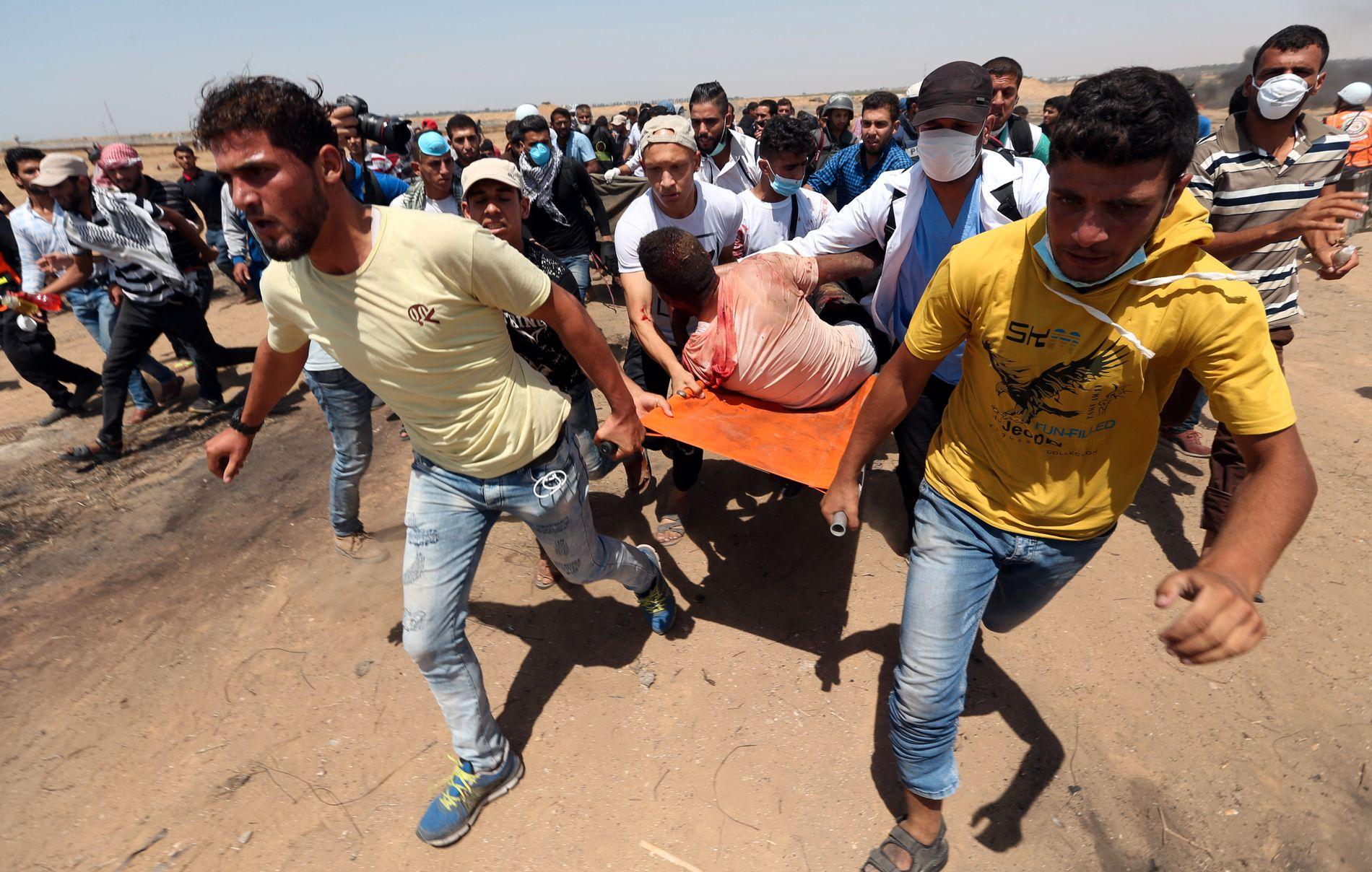 FRAKTES UT: Palestinere evakuerer demonstranten som fikk en tåregassgranat i kinnet.